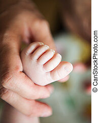 newborn baby feet in female hands