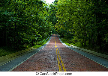 Red Brick Road Through Green Trees - Image of a red brick...