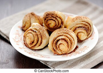 Cinnamon rolls on white plate with stripe napkin