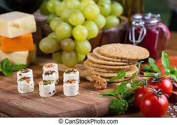 selection of soft cheese with fruits, spices and meat