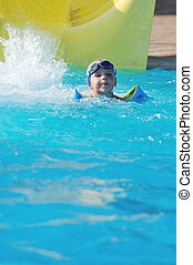 water slide fun on outdoor pool - happy child have fun on...