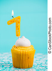 first birthday cup cake with number one candle on blue backgroun