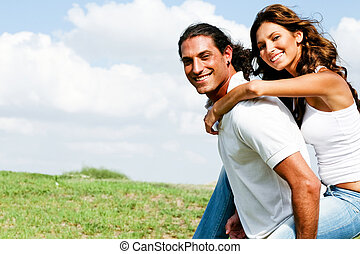 Loving couple - Smiling couple enjoying piggyback ride on...