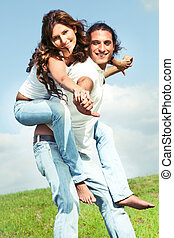 Young male carrying woman - Boyfriend giving piggy ride to...