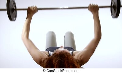 woman doing exercise with barbell - fit woman doing exercise...