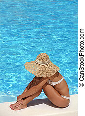 Woman in hat relaxing beside the pool