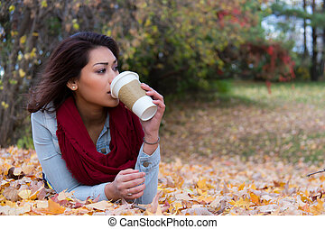 Stylish woman drinking coffee while lying down on autumn leaves