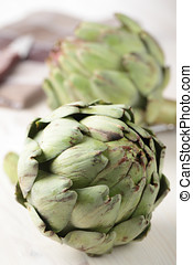 Artichokes - Two raw artichokes on a wooden table