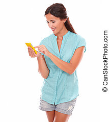 Young hispanic woman sending text message using a yellow...