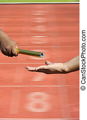 Relay-athletes hands sending action on blur race track...
