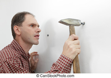 Hard working - Worker hammering the wall plumb