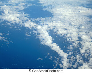 Fluffy little Clouds spread in the sky over the ocean -...