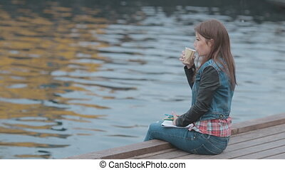 Cute girl sitting on wooden pier with picture and drinking coffee from a cup
