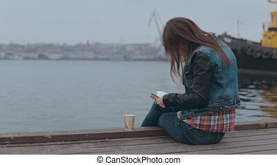Absorbed in drawing girl sitting on a wooden pier near the sea