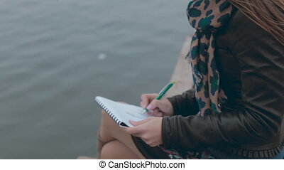 Feminine girl sitting at berth near the sea and drawing...