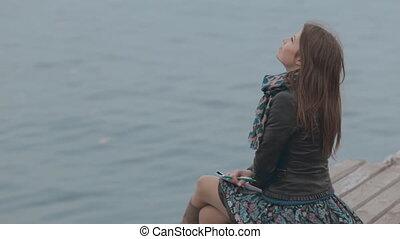 Charming girl siting at berth near the sea and feeling happy...