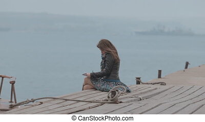 Romantic girl in skirt sitting on the pier near the sea and drawing, beside boat sailing