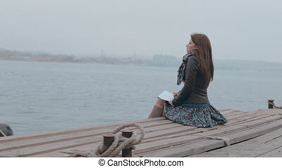 Romantic girl in skirt sitting on the pier near the sea and...