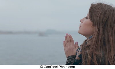 Close up of feminine girl sitting on a wooden pier near the sea and the heating hands