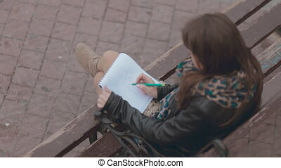 Romantic girl sitting on a bench and drawing pair of lovers...