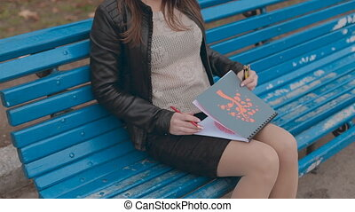 Absorbed in drawing girl sitting on a bench in autumn park