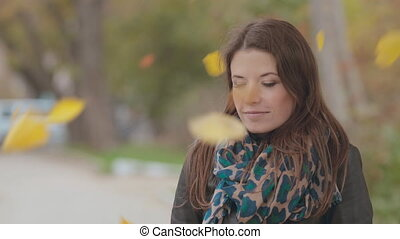 Mysterious girl stands under falling leaves - Mysterious...