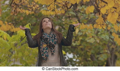 Cheerful girl standing under falling leaves and rejoices -...