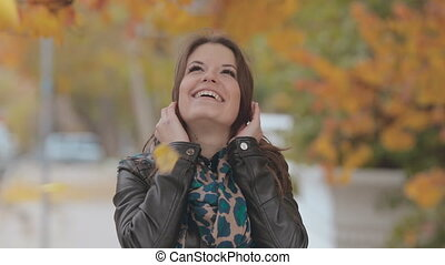Beautiful girl standing under falling leaves and laughing -...