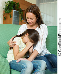 Woman comforting  crying daughter at home