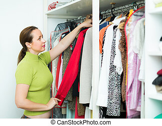 Woman arranging clothes at wardrobe - Orderly woman...