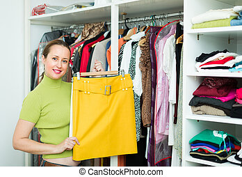 Female choosing apparel at store - Smiling ordinary woman...