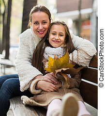 woman with  girl posing in autumn park