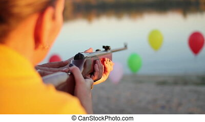 rifle shooting at balloons near the river