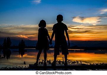 Brother and sister holding hands together with sun set
