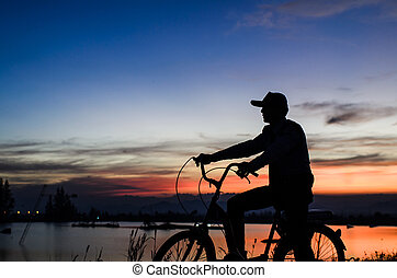 Cycler silhouette in sunrise against sun set cloudy sky