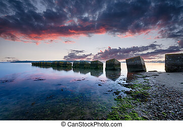 Studland Sunrise - A fiery sunrise over concrete cubes, old...