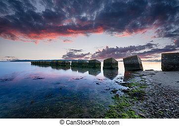 Studland Sunrise - A fiery sunrise over concrete cubes, old...