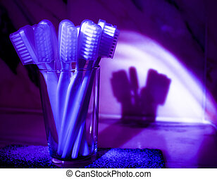 Toothbrushes with bluish purple shadow reflected on the wall...