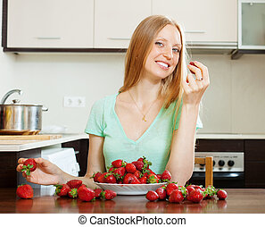 Positive blonde girl eating strawberry in home kitchen
