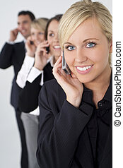 Beautiful Blond Woman On Cell Phone With Team Behind Her - A...