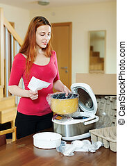 woman unpacking and reading manual for new crock-pot -...