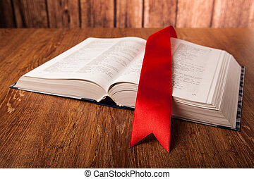 large book with bookmark on a wood background