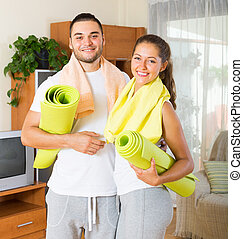 Smiling couple with towels before yoga class - Smiling...