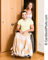 Woman with disabled husband at the door - Young woman and...