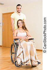 Man and his wife in wheelchair at the door - Young positive...