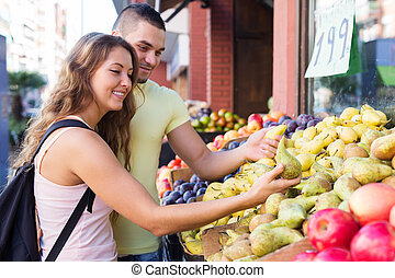 Young family picking fruits out on market and smiling