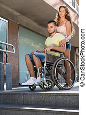 Young man on invalid chair - Young girl and boyfriend in...