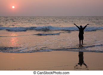Sunset in Goa - Happy girl have fun on the beach at dusk...