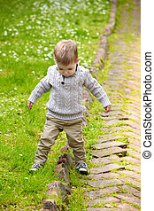 Trendy 2 years old baby boy playing in park
