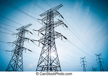 high voltage electricity transmission pylon silhouetted -...